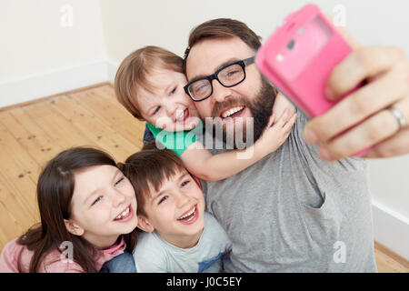 Mid adult man and three children taking smartphone selfie - Stock Photo