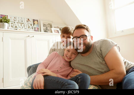 Portrait of mid adult man with son and daughter reclining on beanbag chair - Stock Photo