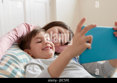 Boy and sister reclining on beanbag chair looking at digital tablet - Stock Photo