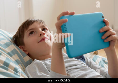 Boy reclining on beanbag chair looking up from digital tablet - Stock Photo