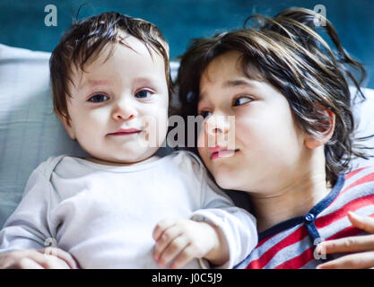 Portrait of boy lying in bed looking sideways at baby brother - Stock Photo