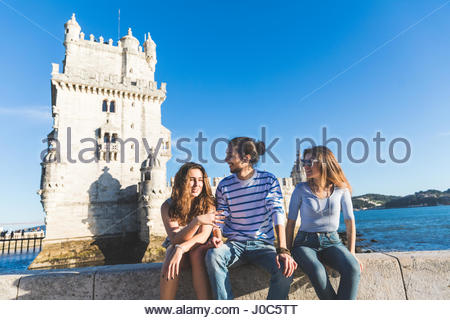 Three friends, sitting on wall by sea, Belem Tower in background, Lisbon, Portugal - Stock Photo