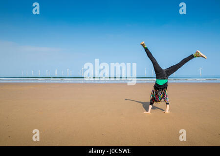 Mature woman doing cartwheel on Redcar beach, North Yorkshire, UK - Stock Photo