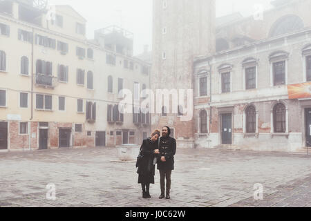 Portrait of couple in misty square, Venice, Italy - Stock Photo