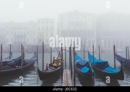 Rows of gondolas on misty canal, Venice, Italy - Stock Photo