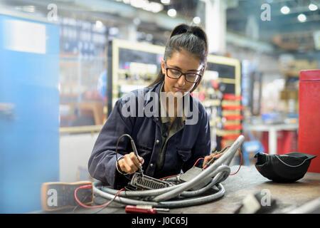 Female apprentice electrician in car factory - Stock Photo