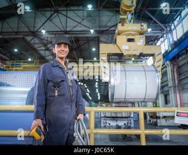 Female apprentice electrician in car factory, portrait - Stock Photo