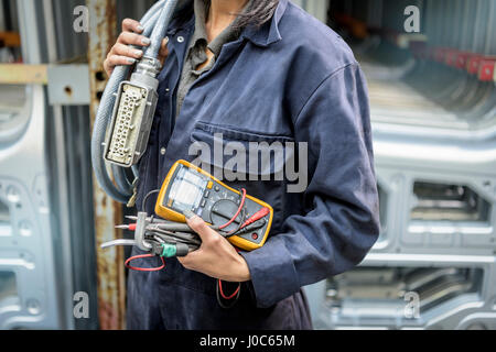 Female apprentice electrician holding equipment in car factory, close up - Stock Photo
