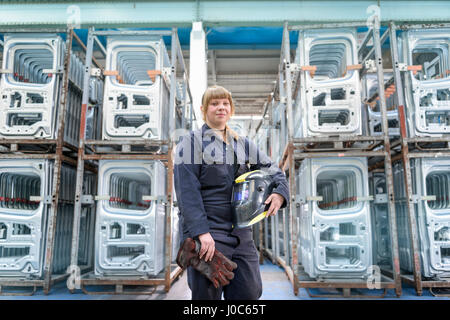 Female apprentice welder holding equipment in car factory, portrait - Stock Photo