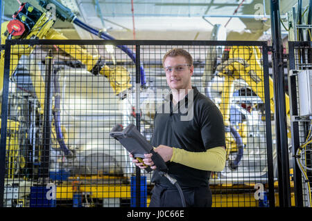 Portrait of apprentice engineer operating robots on production line in car factory - Stock Photo