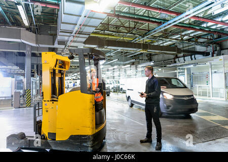 Apprentice engineer with forklift truck in car factory - Stock Photo