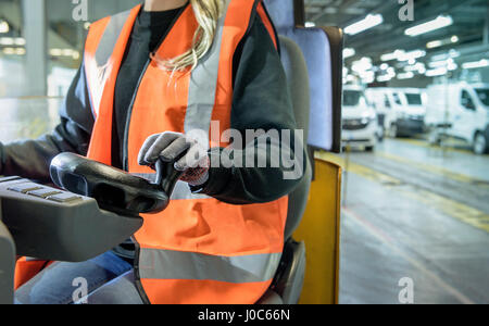 Female forklift driver in car factory, close up - Stock Photo