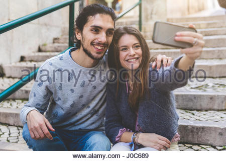 Young couple, sitting on steps, taking selfie with smartphone, Lisbon, Portugal - Stock Photo