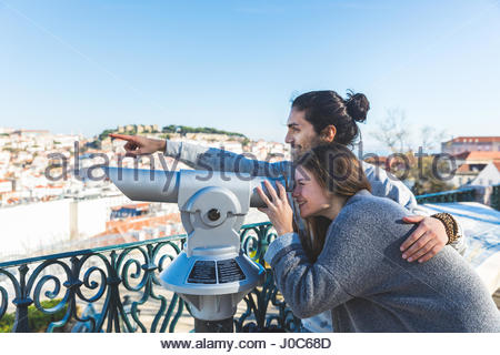 Young couple, sightseeing, looking through coin operated telescope, Lisbon, Portugal
