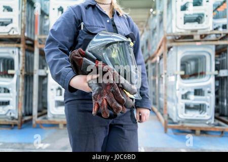 Female apprentice welder holding equipment in car factory - Stock Photo