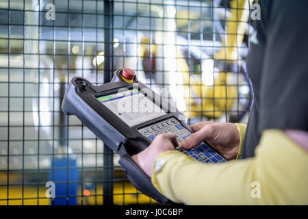 Apprentice engineer operating robots on production line in car factory, close up - Stock Photo