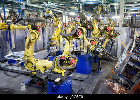 Robots welding body panels on production line in car factory - Stock Photo