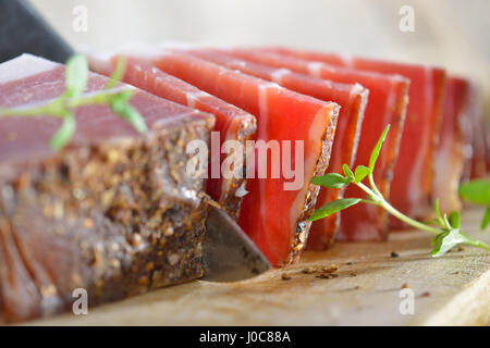 Delicious, according to traditional recipes prepared farmhouse bacon from South Tirol cut on a wooden board - Stock Photo