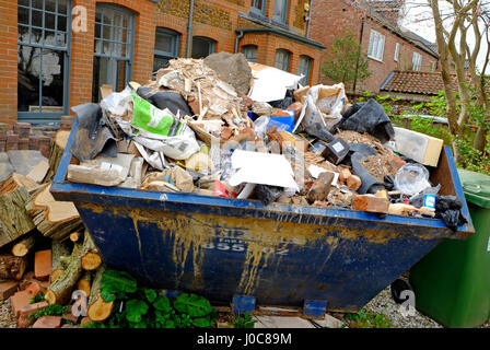 large builders skip in house front garden, norfolk, england - Stock Photo