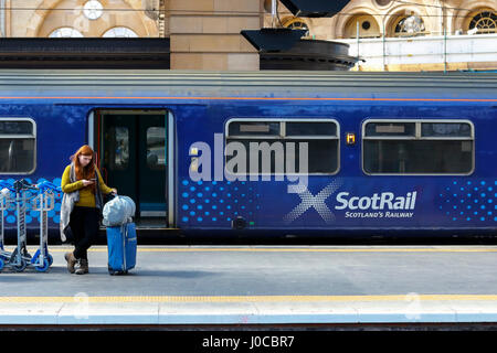 Woman waiting on platform at Glasgow Central railway station, Glasgow with a Scotrail carriage behind her. Glasgow, - Stock Photo