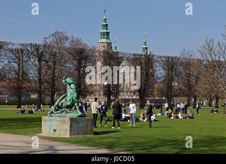 Young people enjoy the warm spring sun on Palm Sunday in Kongens Have, the King's garden, Copenhagen, Denmark. The - Stock Photo