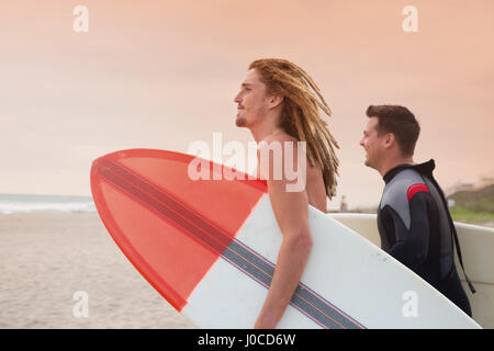 Male lifeguard and surfer looking out to sea from beach - Stock Photo