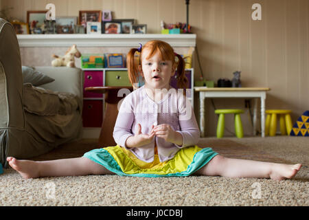 Portrait of young girl with red hair, sitting on carpet, legs outstretched - Stock Photo