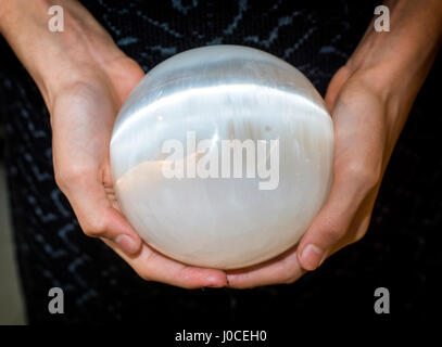 Crop hands holding selenite sphere - Stock Photo