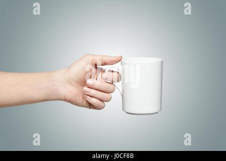 Woman holding a white mug - Stock Photo