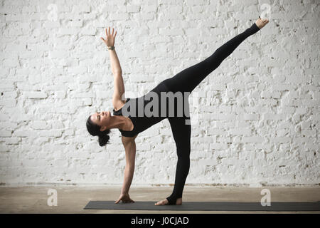 Young yogi attractive woman in Half Moon pose, loft background - Stock Photo