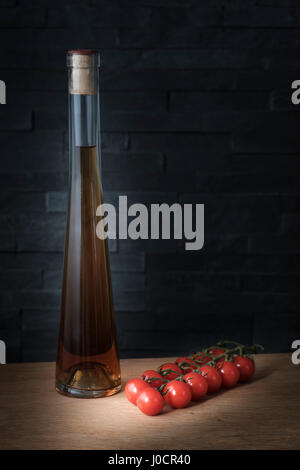 bottle of olive oil and a twig of cherry tomatoes on a wooden board against a dark background, healthy eating concept - Stock Photo