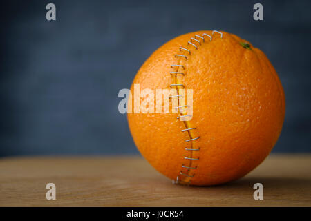 orange with stainless steel stitches that hold the husk together - Stock Photo