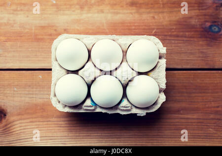 close up of white eggs in egg box or carton - Stock Photo