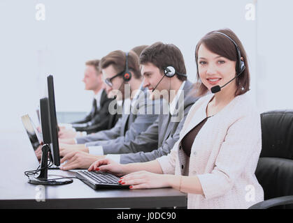 close-up of a woman associate and colleague with headset in a call center sitting in front of computer on white - Stock Photo