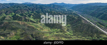 Highway runs straight through the southern California hills into the distance. - Stock Photo