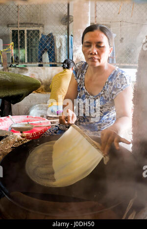 Vertical view of ladies making traditional rice paper in Vietnam. - Stock Photo