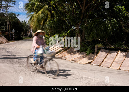 Horizontal street view of traditional rice paper drying in the sun on the roadside in Vietnam. - Stock Photo