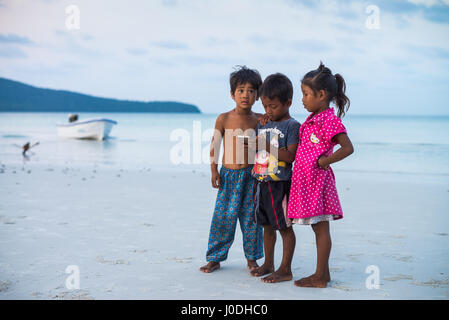 Local child with smartphone on the beach of the Koh Rong Sanloem Island, Cambodia, Asia. - Stock Photo