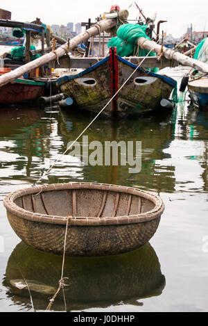 Vertical close up of a traditonal coracle tied up in Da Nang, Vietnam - Stock Photo