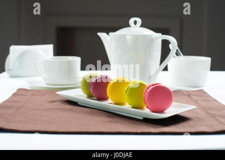 Colorful macaroons on a white square plate Sweet macarons and flowers. Against the background of a tea set white - Stock Photo