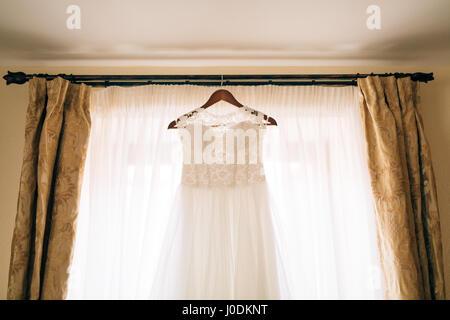 The bride's dress hangs on the cornice - Stock Photo