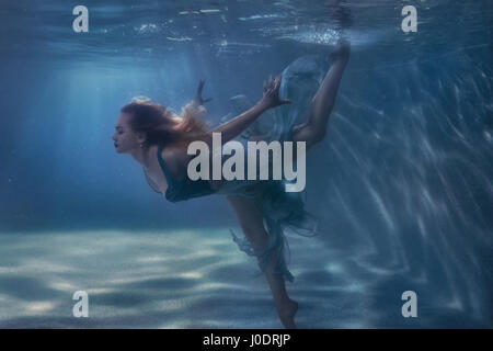 Woman in a dress is dancing underwater. - Stock Photo