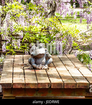 Old stone frog sitting on a old rustic picnic table in the counrty - Stock Photo