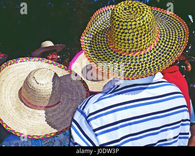 A group of people wearing colorful straw hats during a flower festival parade in Baguio City, Philippines - Stock Photo