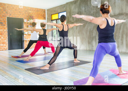 Fitness asian female group doing warm up yoga pose in row at the yoga class. selective focus - Stock Photo