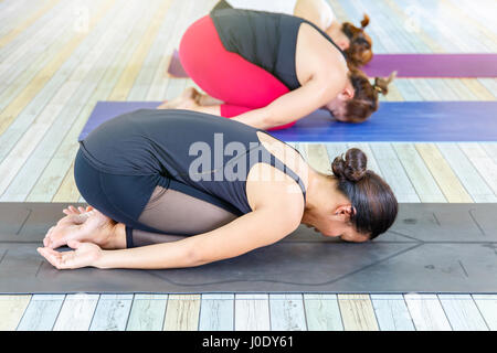 Group of young asians woman practicing during their yoga class in a gym - Stock Photo