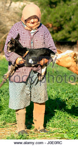 Europe, Greece, View Of Elderly Turkish Woman Holding Baby Goat - Stock Photo