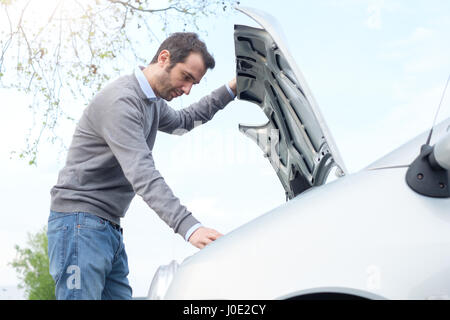 Stressed man checking engine after vehicle breakdown - Stock Photo