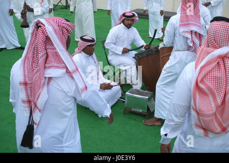 Traditional Bahrain dance accompanied by drums and mizmar. The men are wearing dishdashas, ghutra (keffiyeh) and - Stock Photo