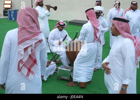 Traditional Bahrain dance accompanied by drums and mizmar (wind instrument). The men are wearing dishdashas, ghutra - Stock Photo